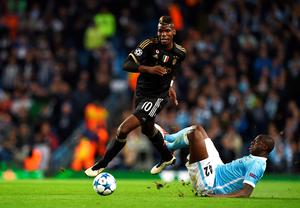 Juventus' midfielder from France Paul Pogba (L) is tackled by Manchester City's Ivorian midfielder Yaya Toure during a UEFA Champions League group stage football match between Manchester City and Juventus at the Etihad stadium in Manchester, north-west England on September 15, 2015.    AFP PHOTO / PAUL ELLISPAUL ELLIS/AFP/Getty Images