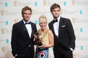 LONDON, ENGLAND - FEBRUARY 16: Presenters Douglas Booth (R), Sam Claflin (L) and costume designer Catherine Martin, pose with winner of the Costume Design award, in the winners room at the EE British Academy Film Awards 2014 at The Royal Opera House on February 16, 2014 in London, England.  (Photo by Anthony Harvey/Getty Images)