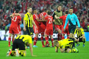 Bayern Munich players celebrate on the pitch after the final whistle as Borussia Dortmund players look dejected during the UEFA Champions League Final at Wembley Stadium, London. PRESS ASSOCIATION Photo. Picture date: Saturday May 25, 2013.