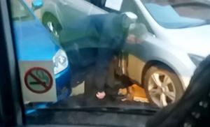 A man , believed to be Gerry Kelly using bolt cutters on a clamped car close to the MAC in Belfast on February 1st 2018 (Photo by Belfast Telegraph)