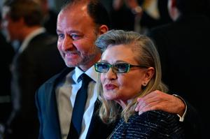 """(FILES) This file photo taken on May 14, 2016 shows US actress Carrie Fisher poses with US actor and director Fisher Stevens for the screening of the film """"Agassi (The Handmaiden - Mademoiselle)"""" at the 69th Cannes Film Festival in Cannes, southern France.  Hollywood star Carrie Fisher -- best known for her portrayal of Princess Leia in the """"Star Wars"""" saga -- died December 27, 2016y, days after suffering a massive heart attack on a transatlantic flight, according to a family statement given to People magazine. """"It is with a very deep sadness that Billie Lourd confirms that her beloved mother Carrie Fisher passed away at 8:55 this morning,"""" family spokesman Simon Halls said in a statement on behalf of Fisher's daughter.  / AFP PHOTO / ALBERTO PIZZOLIALBERTO PIZZOLI/AFP/Getty Images"""