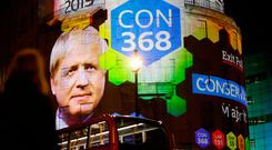 People watch as the BBC's exit poll results are projected on the outside of one of its buildings on Thursday night. The Tories were predicted to win 368 seats but finished with 365