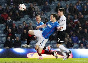 Rangers' Jon Daly and Ayr United's Brian Gilmore battle for the ball during the Scottish League One match at Ibrox, Glasgow.
