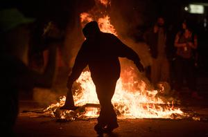 A man tosses a cone into a burning trash fire at an intersection during an anti-Trump protest in Oakland, California on November 9, 2016.  Thousands of protesters rallied across the United States expressing shock and anger over Donald Trump's election, vowing to oppose divisive views they say helped the Republican billionaire win the presidency. / AFP PHOTO / Josh EdelsonJOSH EDELSON/AFP/Getty Images