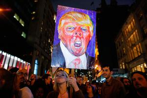 TOPSHOT - A woman holds a poster as she takes part in a protest against President-elect Donald Trump in New York City on November 9, 2016. / AFP PHOTO / KENA BETANCURKENA BETANCUR/AFP/Getty Images