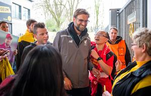 Liverpool's coach Jurgen Klopp , center, is surrounded by fans as he arrives for a news conference in Dortmund, Germany, Wednesday, April 6, 2016. ( Bernd Thissen/dpa via AP)