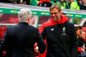 """Stoke City manager Mark Hughes (left) shakes hands with Liverpool manager Jurgen Klopp before the Capital One Cup, semi final, first leg match at The Britannia Stadium, Stoke. PRESS ASSOCIATION Photo. Picture date: Tuesday January 5, 2015. See PA story SOCCER Stoke. Photo credit should read: Martin Rickett/PA Wire. RESTRICTIONS: EDITORIAL USE ONLY No use with unauthorised audio, video, data, fixture lists, club/league logos or """"live"""" services. Online in-match use limited to 75 images, no video emulation. No use in betting, games or single club/league/player publications."""