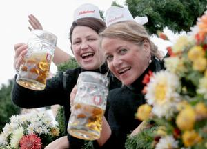 MUNICH, GERMANY - SEPTEMBER 21:  Waitresses wave beer mugs during the opening parade of the Oktoberfest 2013 beer festival at Theresienwiese on September 21, 2013 in Munich, Germany. The Munich Oktoberfest, which this year will run from September 21 through October 6, is the world's largest beer fest and draws millions of visitors.  (Photo by Johannes Simon/Getty Images)
