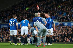 Referee Martin Atkinson shows Newcastle United's Fabricio Coloccini (second from right) a red card during the Barclays Premier League match at Goodison Park, Liverpool. Lynne Cameron/PA Wire.