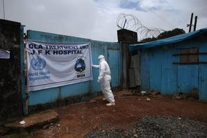 A member of a burial team prepares to collect Ebola victims from a treatment centre for cremation on October 2, 2014 in Monrovia, Liberia. Eight Liberian Red Cross burial teams under contract with the country's Ministry of Health collect the bodies of Ebola victims each day in the capital. More than 3,200 people have died in West Africa due to the epidemic.  (Photo by John Moore/Getty Images)