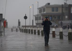 "NORDDEICH, GERMANY - DECEMBER 05:  A man covers his face against the heavy wind and rain on North Sea coastline on December 5, 2013 near Norddeich, Germany. Germany is bracing for ""Xaver"", a heavy storm meteorologists are predicting could be the most severe storm for the region in decades.  (Photo by David Hecker/Getty Images)"
