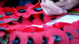 A veteran holds a poppy wreath during a Remembrance Day ceremony