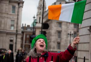 A woman waves an Irish flag at the Mayor of London's St Patrick's Day Parade and Festival in London. Daniel Leal-Olivas/PA Wire.