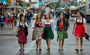 "MUNICH, GERMANY - SEPTEMBER 21:  A Visitors in bavarian style clothes (""Dirndl"") go to the Oktoberfest 2013 beer festival at Theresienwiese on September 21, 2013 in Munich, Germany. Many visitors arrived early to the festival to secure good places in the beer tents. Munichs mayor Christian Ude launches the Oktoberfest at 12.00 o'clock in the Schottenhamel-tent by tapping the first barrel of beer with the traditional ""O'zapft is!"" (""It's tapped!"") The Munich Oktoberfest, which this year will run from September 21 through October 6, is the world's largest beer fest and draws millions of visitors.  (Photo by Joerg Koch/Getty Images)"