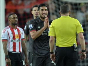 Liverpool's German midfielder Emre Can (C) gestures to referee Kevin Friend after a foul for which the referee showed a yellow card during the English Premier League football match between Sunderland and Liverpool at the Stadium of Light in Sunderland, north east England, on December 30, 2015. AFP PHOTO / OLI SCARFF  RESTRICTED TO EDITORIAL USE. No use with unauthorized audio, video, data, fixture lists, club/league logos or 'live' services. Online in-match use limited to 75 images, no video emulation. No use in betting, games or single club/league/player publications.OLI SCARFF/AFP/Getty Images