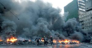 Protesters throw tires onto a fire during clashes with police in central Kiev, Ukraine, Thursday, Jan. 23, 2014. Thick black smoke from burning tires engulfed parts of downtown Kiev as an ultimatum issued by the opposition to the president to call early elections or face street rage was set to expire with no sign of a compromise on Thursday.  (AP Photo/Efrem Lukatsky)