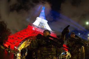 A French soldier enforcing the Vigipirate plan, France's national security alert system, is pictured on November 17, 2015 in Paris in front of the Eiffel Tower, which is illuminated with the colors of the French national flag in tribute to the victims of the November 13 Paris terror attacks. AFP/Getty Images