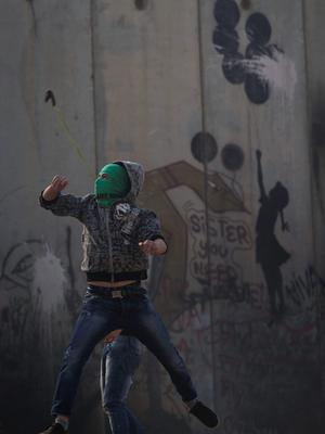 Palestinians throw stones next to the separation barrier during clashes with Israeli forces following a protest against Israeli restrictions to Al-Aqsa Mosque in Jerusalem, at the Qalandia checkpoint near the West Bank city of Ramallah, Friday, Nov. 14, 2014.  (AP Photo/Majdi Mohammed)