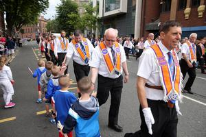 Members of the public watch Orangemen and bandsmen in Belfast City Centre as they take part in  the annual Twelfth of July parade in Belfast. The parades celebrate William of Orange's victory over King James II at the Battle of the Boyne in 1690. Photo by Kelvin Boyes / Press Eye.
