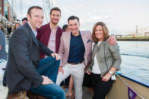 John Minnis (second from right) with directors Chris Kirk, Stephen McLean and Emma Coote aboard a private party boat during the Belfast Tall Ships festival as John Minnis Estate Agents toasts 10 years in business