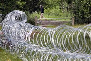 A man walks past razor wire which has been laid in fields near the Lough Erne resort in County Fermanagh the venue for next weeks G8 Summit. PRESS ASSOCIATION Photo. Picture date: Wednesday June 12, 2013. See PA story ULSTER G8. Photo credit should read: Paul Faith/PA Wire