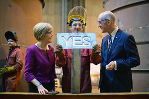 RENFREW, SCOTLAND - SEPTEMBER 16:  Deputy First Minister Nicola Sturgeon and Cabinet Secretary for Finance John Swinney, look on as 19 year old apprentice fabricator Craig McKee holds a yes sign during their visit to Steel Engineering on September 16, 2014 in Renfrew, Scotland. With just two days of campaigning left before polling stations open and voters across the country will hold Scotlands future in their hands.  (Photo by Jeff J Mitchell/Getty Images)