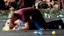 A man lays on top of a woman as others flee the Route 91 Harvest country music festival grounds after a active shooter was reported on October 1, 2017 in Las Vegas, Nevada.