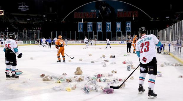 Belfast Giants players help to clear up after the Teddy Bear Toss during Saturday night's game against the Sheffield Steelers at the SSE Arena (William Cherry/Presseye)