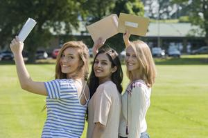 A Level student's at  Banbridge academy, Co Down celebrate getting their results. Pictured are A and A star students Hanna Bennett with Radhika Gupta [who got four A stars] and Amy Campbell. Picture Mark Marlow
