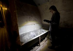 Lead guide Siddy Holloway shines a torch on an old bath at Down Street disused underground station in Mayfair, London, where Winston Churchill took refuge at the height of the Blitz, for the launch of a new season of Hidden London disused station tours. PRESS ASSOCIATION Photo. Picture date: Wednesday April 13, 2016. Down Street had a short life as a working station from 1907 to 1932, but became critical to winning the Second World War when it was covertly transformed into the Railway Executive Committee's bomb-proof bunker. Photo credit should read: Yui Mok/PA Wire