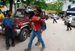 An Indian bystander carries an injured youth who fell downstairs at Siliguri Hospital as a tremor struck in Siliguri on May 12, 2015. A new earthquake of 7.3-magnitude and several powerful aftershocks hit devastated Nepal on May 12, killing at least four people and sending terrified residents running into the streets of the traumatised capital. The quake was felt as far away as New Delhi, and officials said it caused buildings to collapse in Chinese-controlled Tibet.AFP PHOTO / Diptendu DUTTADIPTENDU DUTTA/AFP/Getty Images