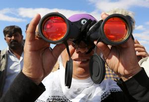 A Turkish Kurdish woman uses binoculars to watch the fighting between Islamic militants and Kurdish forces to the west of Kobani, Syria, at the Turkey-Syria border near Suruc, Turkey, Tuesday, Sept. 30, 2014. U.S.-led coalition airstrikes targeted fighters, vehicles and artillery pieces of the Islamic State group on both sides of the Syria-Iraq frontier Tuesday, including around a beleaguered Kurdish town near the Syrian-Turkish border that is under assault by the militants, activists said.  (AP Photo/Burhan Ozbilici)