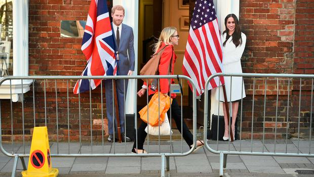 TOPSHOT - A pedestrian walks past cut-out figures of Britain's Prince Harry and US actress Meghan Markle in Windsor on May 17, 2018, two days before the Royal wedding.  Britain's Prince Harry and US actress Meghan Markle will marry on May 19 at St George's Chapel in Windsor Castle. / AFP PHOTO / Oli SCARFFOLI SCARFF/AFP/Getty Images