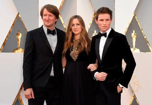 Thomas Hooper (L), Eddie Redmayne (R) and Hannah Redmayne arrive on the red carpet for the 88th Oscars on February 28, 2016 in Hollywood, California. AFP PHOTO / VALERIE MACONVALERIE MACON/AFP/Getty Images