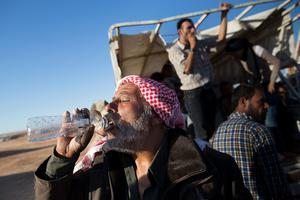 SANLIURFA, TURKEY - OCTOBER 01:  A man drinks water after crossing the border from Syria into Turkey on October 1, 2014 near Suruc, Turkey. Kurdish troops are engaged in a battle against fighters of the Islamic State (IS, also called ISIS and ISIL) to defend the strategic nearby Kurdish border town of Kobani (also called Ayn Al-Arab), which ISIS has surrounded on three sides. The Turkish Parliament is due to vote on a measure on October 2, which would allow Turkish ground forces to enter Syria, creating a buffer zone to protect fleeing refugees from the ISIS advance.  (Photo by Carsten Koall/Getty Images)