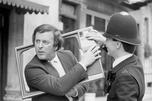 Sir Terry Wogan popping up through a TV screen to the amusement of a policeman after he accepted 100 TV sets on behalf of the NSPCC from Phillips marking the making of the company's 100 millionth TV set (1984)