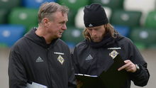 Talking tactics: Michael O'Neill and assistant coach Austin MacPhee go over their notes ahead of the crunch clash at Windsor Park