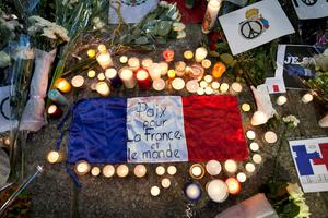 A flag of France is surrounded by candles and flowers outside of the French embassy in Mexico City during a vigil for the victims of the terrorist attacks in Paris, Monday, Nov. 16, 2015. Multiple attacks across Paris on Friday left scores dead and hundreds injured. (AP Photo/Marco Ugarte)