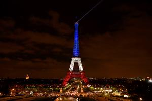 A photo taken on November 16, 2015 in Paris shows the Eiffel Tower illuminated with the colours of the French national flag in tribute to the victims of November 13 Paris terror attacks which killed at least 129 people in scenes of carnage at a concert hall, restaurants and the national stadium. AFP PHOTO / ERIC FEFERBERGERIC FEFERBERG/AFP/Getty Images