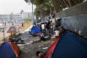 "Migrants gather outside the stadium where they go through a registration procedure by the police on the Greek island of Kos on August 12, 2015. The number of migrants and refugees arriving on Greece's shores has exploded this year, but the Mediterranean country provides virtually no reception facilities and leaves them wallowing in ""totally shameful"" conditions, a UN official said on August 7. The UN refugee agency's division for Europe said 124,000 refugees and migrants have landed in Greece since the beginning of the year. AFP PHOTO / ANGELOS TZORTZINISANGELOS TZORTZINIS/AFP/Getty Images"