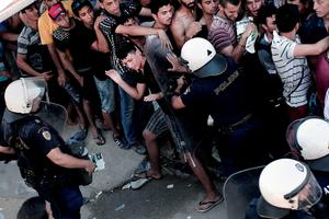A policeman pushes a migrant as hundreds wait to complete a registration procedure by the police at a stadium on the Greek island of Kos on August 12, 2015. Tensions on the tourist island are high with its mayor claiming there were 7,000 migrants stranded on Kos, which has a population of only 30,000 people. A Kos police officer was suspended on August 10 after being filmed slapping and shoving migrants queueing outside the local police station as they waited to be documented so they could go on to Athens. The UN refugee agency's division for Europe said 124,000 refugees and migrants have landed in Greece since the beginning of the year. AFP PHOTO / ANGELOS TZORTZINISANGELOS TZORTZINIS/AFP/Getty Images