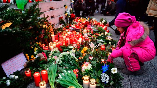 A girl looks at candles at a makeshift memorial for the attack victims, on December 20, 2016 in front of the Kaiser-Wilhelm-Gedaechtniskirche (Kaiser Wilhelm Memorial Church) in Berlin, where a truck crashed into a Christmas market. Twelve people were killed and almost 50 wounded, 18 seriously, when the lorry tore through the crowd on December 19, 2016, smashing wooden stalls and crushing victims, in scenes reminiscent of July's deadly attack in the French Riviera city of Nice. / AFP PHOTO / John MACDOUGALLJOHN MACDOUGALL/AFP/Getty Images
