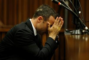 Oscar Pistorius sits with his head in his hands in the dock on the third day of his trial at the high court in Pretoria, South Africa, Wednesday, March 5, 2014. Pistorius is charged with murder for the shooting death of his girlfriend, Reeva Steenkamp, on Valentine's Day in 2013. (AP Photo/Siphiwe Sibeko, Pool)