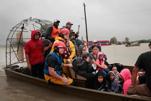 HOUSTON, TX - AUGUST 28:  People are rescued from a flooded neighborhood after it was inundated with rain water, remnants of Hurricane Harvey, on August 28, 2017 in Houston, Texas. Harvey, which made landfall north of Corpus Christi late Friday evening, is expected to dump upwards to 40 inches of rain in areas of Texas over the next couple of days.  (Photo by Scott Olson/Getty Images) *** BESTPIX ***