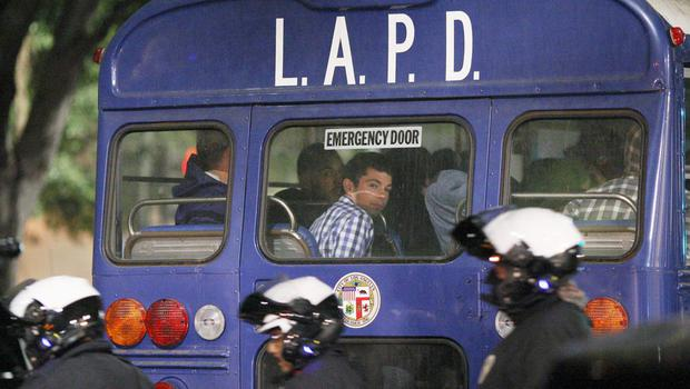 A protester sits in the back of a Los Angles Police Departmet (LAPD) transport bus after arrested at one intersection during a demonstration following the grand jury decision not to indict a white police officer who had shot dead an unarmed black teenager in Ferguson, Missouri in the early morning hours of November 26, 2014 in Los Angeles, California.   (Photo by David McNew/Getty Images)