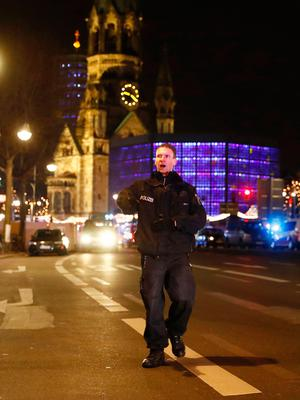 Police blocks a road leading to the site next to the Gedächniskirche church (background) where a truck crashed into a christmas market in Berlin, on December 19, 2016 killing at least nine people and injuring at least 50 people. / AFP PHOTO / Odd ANDERSENODD ANDERSEN/AFP/Getty Images
