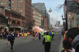 A photographer captures the moment an explosion goes off close to the finish line of the Boston Marathon