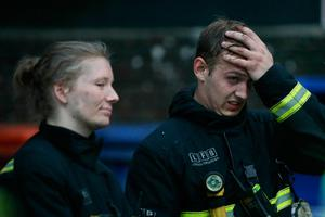 """Firefighters react as a huge fire engulfs the Grenfell Tower early June 14, 2017 in west London.  The massive fire ripped through a 27-storey apartment block in west London in the early hours of Wednesday, trapping residents inside as 200 firefighters battled the blaze. Police and fire services attempted to evacuate the concrete block and said """"a number of people are being treated for a range of injuries"""", including at least two for smoke inhalation.   / AFP PHOTO / Daniel Leal-OlivasDANIEL LEAL-OLIVAS/AFP/Getty Images"""