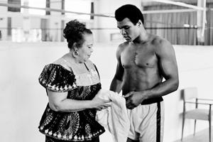 """This file photo taken on October 27, 1974 shows US boxing heavyweight champion Muhammad Ali (born Cassius Clay) standing with her mother Odessa Grady Clay during a training session three days before the heavy weight world championship in Kinshasa.  Boxing icon Muhammad Ali died on Friday, June 3, a family spokesman said in a statement. """"After a 32-year battle with Parkinsons disease, Muhammad Ali has passed away at the age of 74,"""" spokesman Bob Gunnell said. / AFP PHOTO / STRSTR/AFP/Getty Images"""