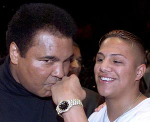 """This file photo taken on January 14, 1999 shows Heavyweight boxing legend Muhammad Ali (L) kissing the fist of Mexican-American lightweight champion Fernando Vargas during the Mike Tyson-Francois Botha weigh-in at the MGM Grand  Casino in Las Vegas. Boxing icon Muhammad Ali died on Friday, June 3, a family spokesman said in a statement. """"After a 32-year battle with Parkinsons disease, Muhammad Ali has passed away at the age of 74,"""" spokesman Bob Gunnell said. / AFP PHOTO / MIKE NELSONMIKE NELSON/AFP/Getty Images"""